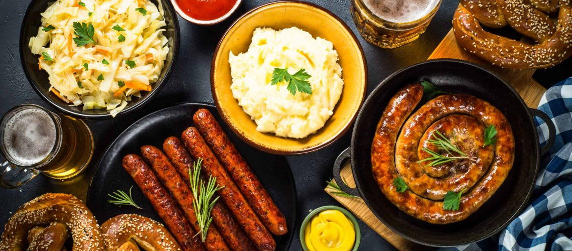 Oktoberfest food. Holiday german dishes - sauerkraut, sausage, pretzel, mashed potato and beer. Top view on black table.